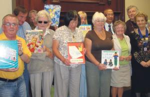 Reading in schools: Lions Club members with Lion Ben (back row, second right) holding some of the books collected.